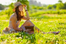 beautiful girl wearing hat with book sitting on grass and looking far away