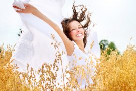 Beautiful Happy Girl on the Wheat Field