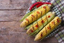 grilled corn with chili peppers on a wooden top view