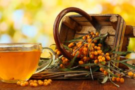 Branches of sea buckthorn with tea and wooden basket on table on bright background