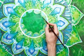 man painting bright green picture with circle pattern, mandala o