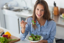 Pretty woman eating a salad in the kitchen