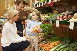 Family Choosing Fresh Vegetables In Farm Shop