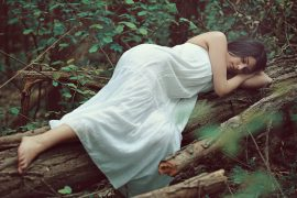 Sleeping woman on dead tree
