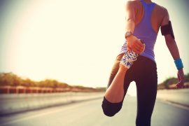 young ftiness woman runner stretching legs before run