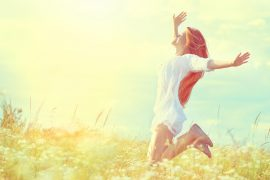 Beauty model girl in white dress jumping on summer field