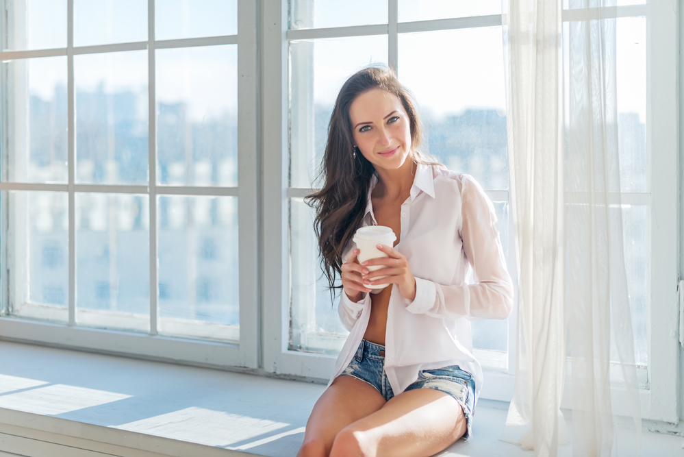 Beautiful girl wearing sexy home outfit sitting next to the window morning with a cup coffee in her hands full of light