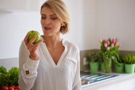 Happy young woman eating apples