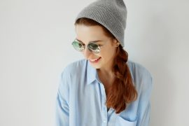 Close up of young pretty woman wearing hipster clothes and trendy round shades smiling and looking down while posing against white blank copy space wall background for your text or advertsing content