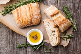 Sliced bread Ciabatta and extra virgin Olive oil on wooden backg