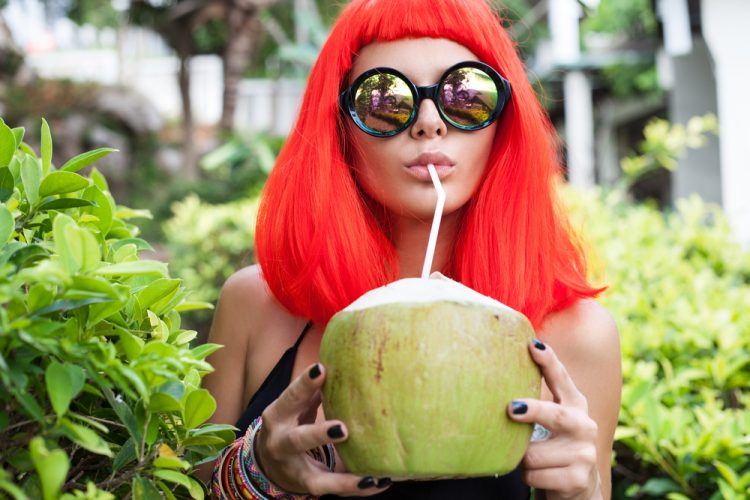 Woman in red wig drinking coconut juice