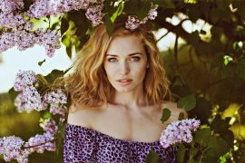Portrait of beautiful delicate red-haired girl with freckles and clear blue eyes in the sprigs of lilac in the summer, close-up