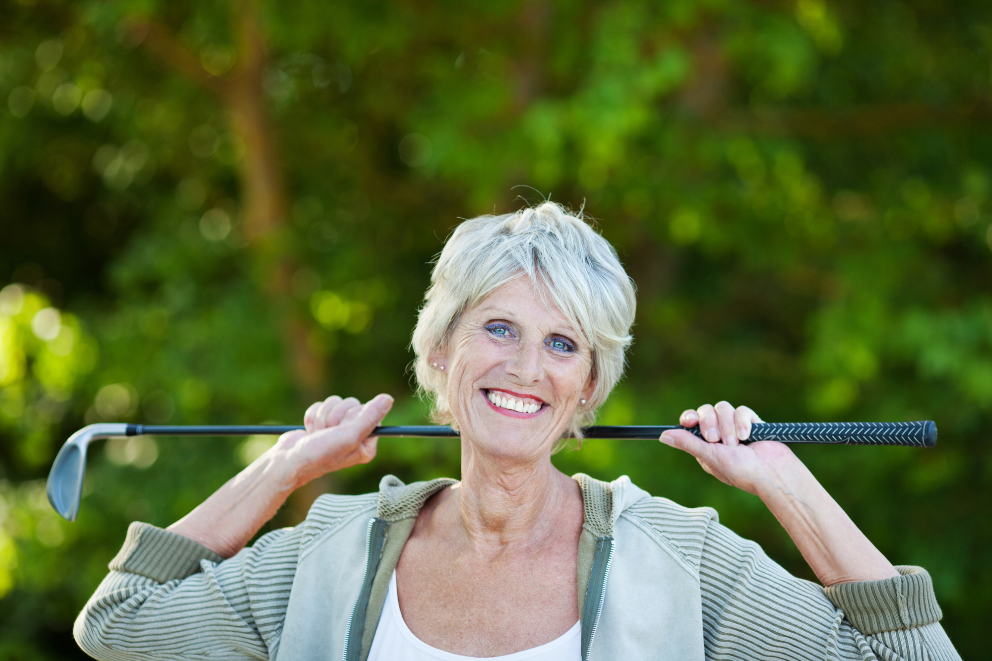 Happy older woman with a golf stick