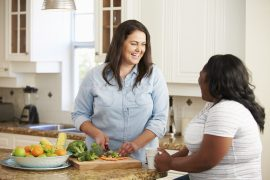 Two Overweight Women On Diet Preparing Vegetables in Kitchen