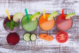 Vegetables, fresh juices mix fruit healthy drinks on wood table.