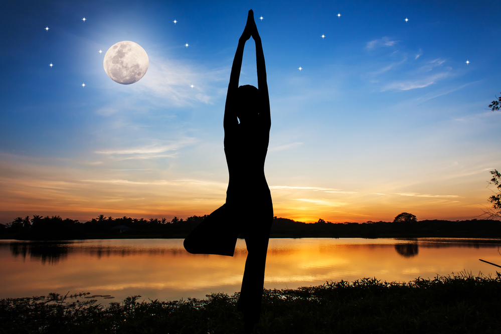 Silhouette young woman practicing yoga  on night full moon backg
