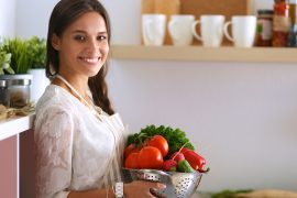 Smiling young woman holding vegetables standing in kitchen