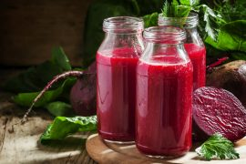 Vitamin beetroot smoothie in glass bottles on the old wooden bac