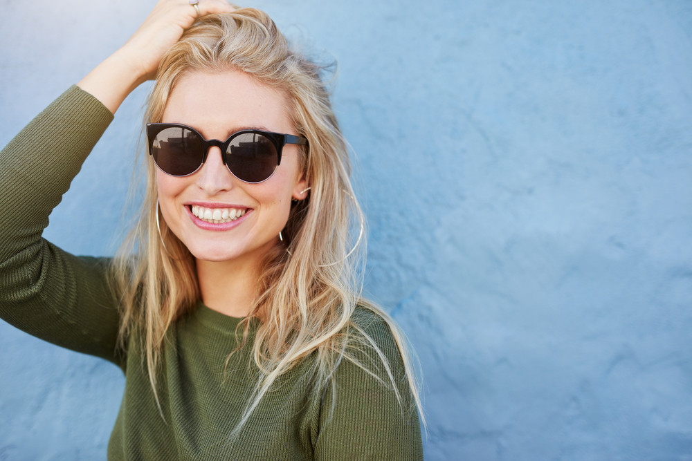 Pretty young woman in sunglasses smiling