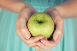 Woman's hands holding a green apple