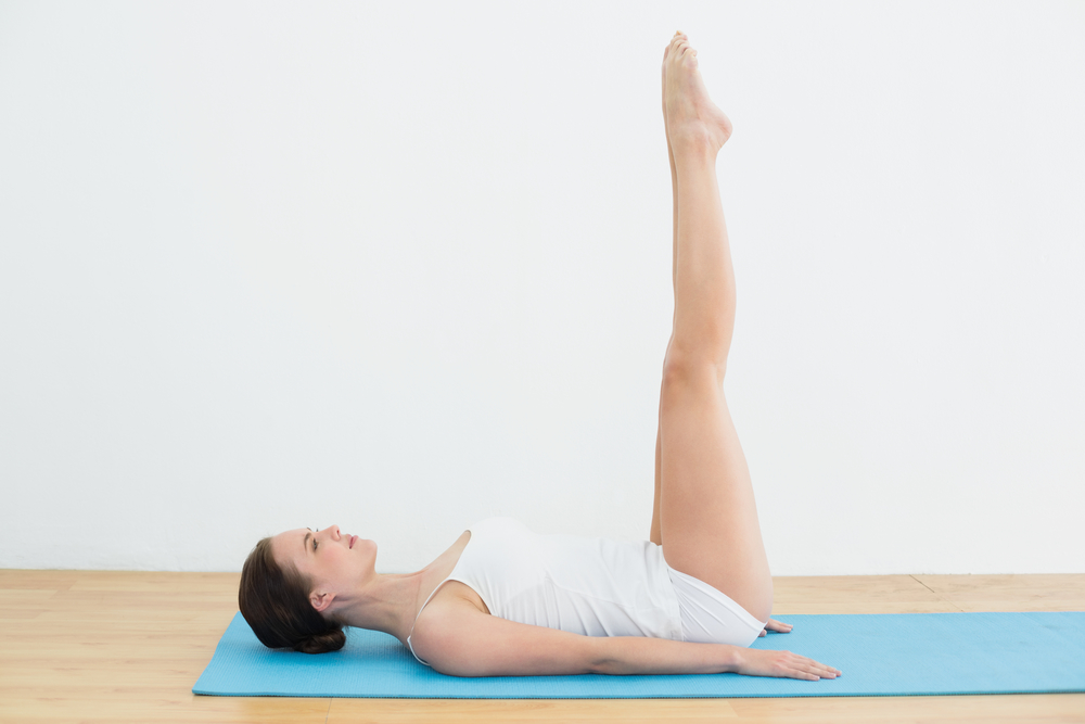 Full length side view of a young woman stretching legs on exercise mat