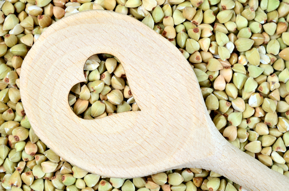 Wooden spoon with heart shape in a green buckwheat
