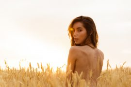 Nude  brunette young girl in a orange field during the sunset, c