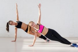 Group of two active sportive women practicing the side plank exercise hand up yoga class in a gym