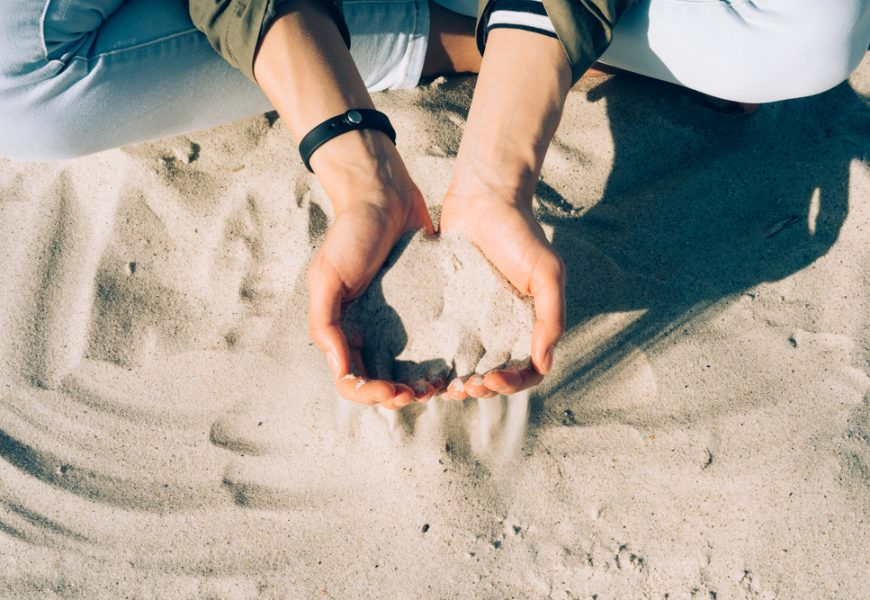 Girl sitting on the beach and the sand passes through the palm