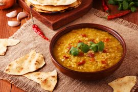 Thick indian red lentil soup with cilantro served with indian f