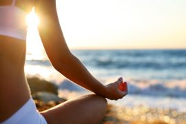 Woman meditating on the beach at sunset.
