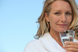 Attractive blonde haired woman with no make up on and drinking a glass of w