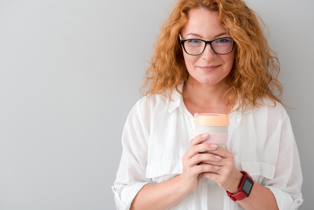 Positive woman holding thermos with tea