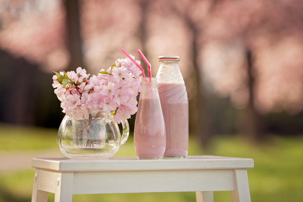 Strawberry smoothie freshly made in a jar, forest spring flowers