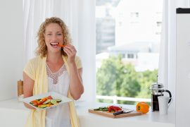 Beautiful woman is eating vegetables