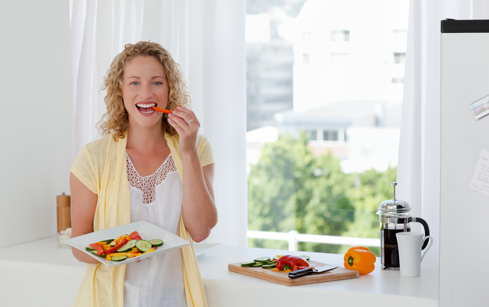 Beautiful woman is eating vegetables