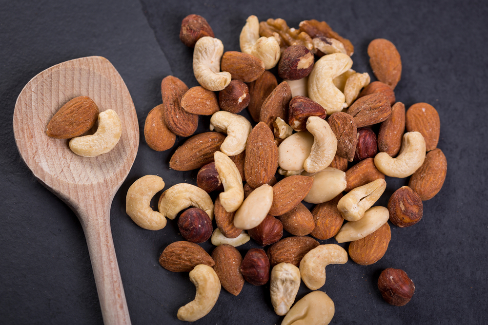Various raw nuts in a pile on dark background