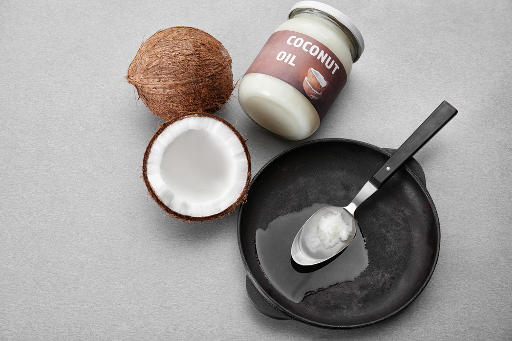 Spoon with coconut oil in frying pan and jar on kitchen table