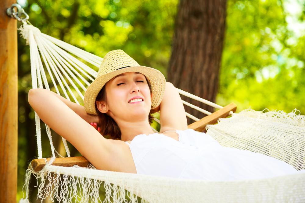 Happy Woman Relaxing in a Hammock