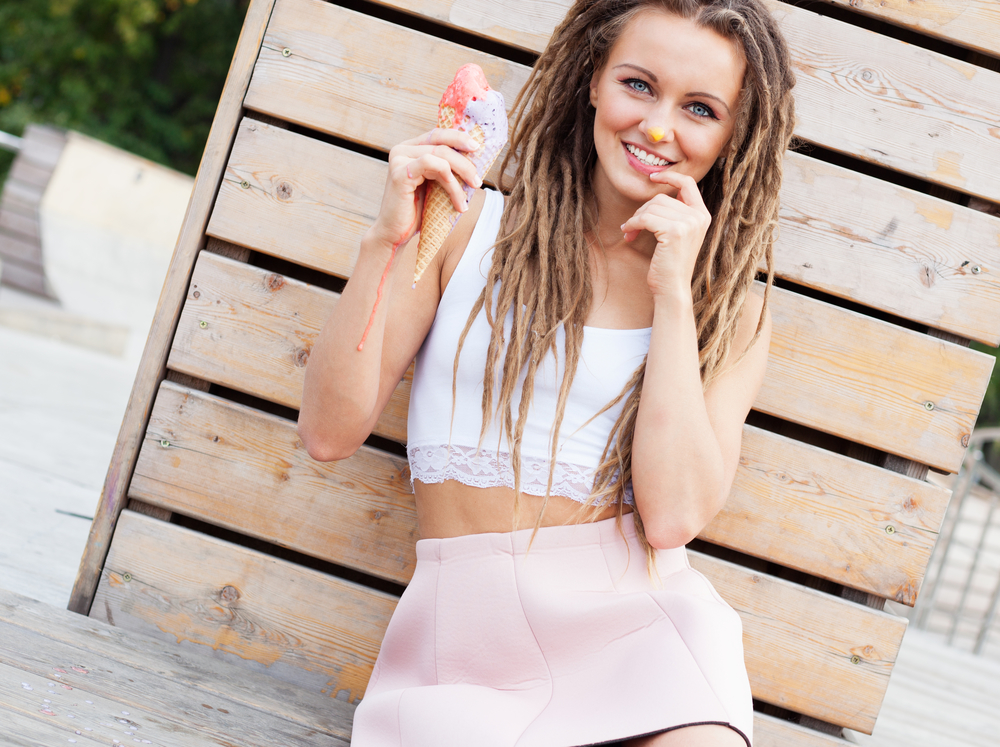 Beautiful girl with dreadlocks in pink skirt sitting on the veranda and eating colorful ice-cream cone on a warm summer evening. Close up. Outdoor.