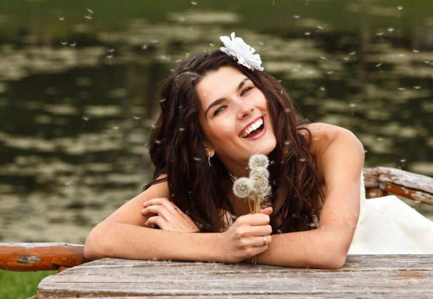 young woman with dandelions summer outdoor, beautiful bride has