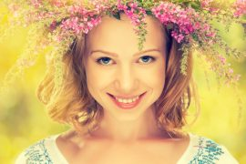 beautiful happy Slavic girl in a wreath of summer flowers
