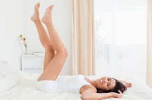 smiling woman legs raised up high and arms under her head lying