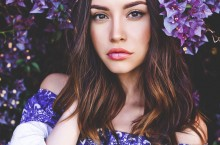 Beautiful young woman surrounded by flowers