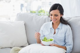 Woman relaxing on the sofa eating salad in her living room