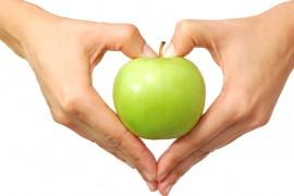 Heart shaped hands holding an apple