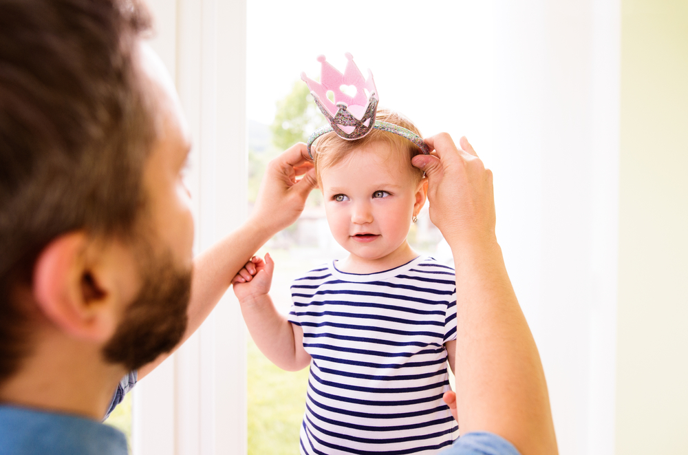 Hipster father with daughter putting crown on her head