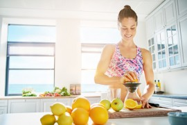 Fit young woman preparing healthy fruit juice
