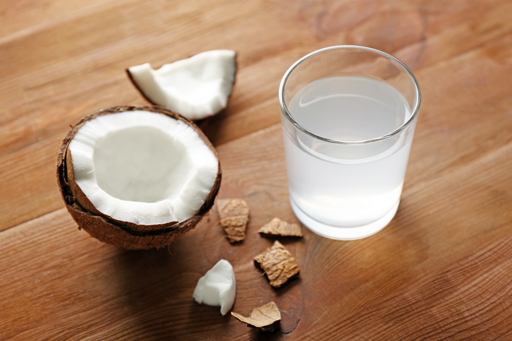 Glass of coconut water and fresh nut on wooden background