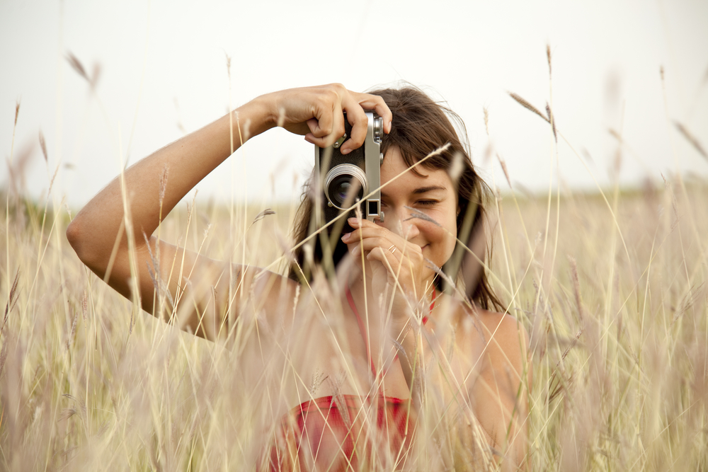 Brunette girl with camera at outdoor.